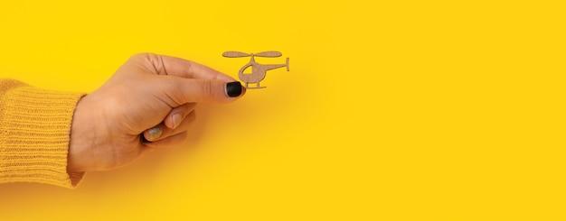 黄色の背景、パノラマのモックアップを手に木製ヘリコプター