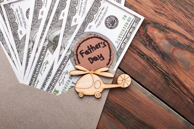 ドル札の近くの木のヘリコプター。父の日カードとバックス。贅沢な生活を。