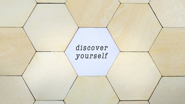Wooden hexagon missing from puzzle, revealing the word reinvent yourself in a conceptual image of personal growth and self discovery