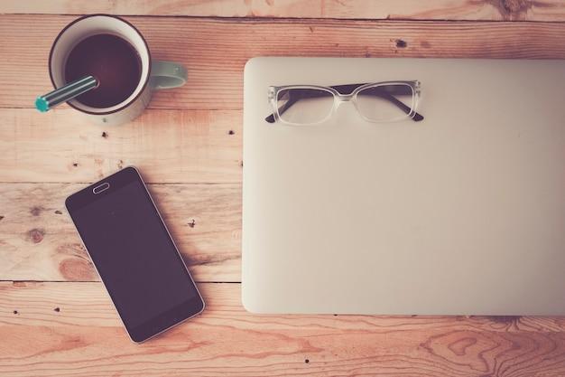 ノートパソコン、コーヒー、スマートフォン、眼鏡を備えた木製の流行に敏感なモダンなオフィスデスクテーブル-現代のテクノロジーの仕事のコンセプトのためのフラットレイヤー写真-多くのデバイスを備えた自宅のワークステーション