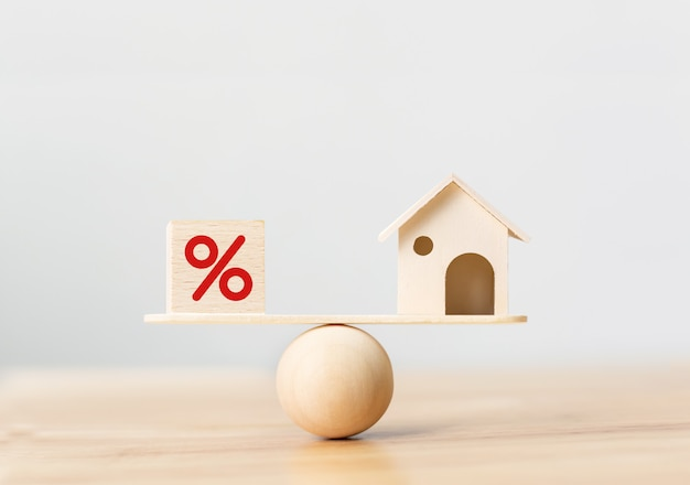 Форма деревянного дома и кубического блока со значком процента на деревянных весах