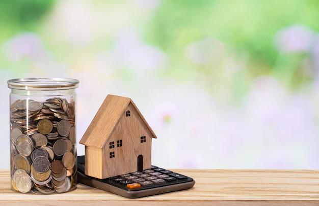 木造住宅モデル、コインホルダー、木製のテーブル上の電卓、お金の概念を保存