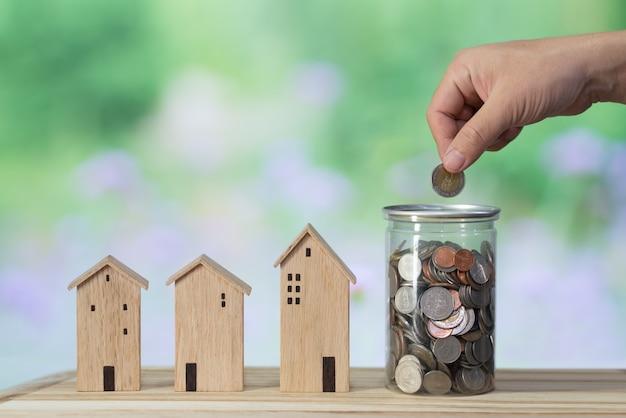 木造住宅モデル、コインホルダー、木製のテーブルに貯金箱、お金の概念を保存