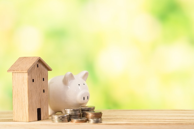 木造住宅モデル、木製のテーブルにお金のコイン、お金の概念を保存