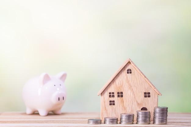 テーブルの上のお金のドル硬貨を持つ木造住宅モデル