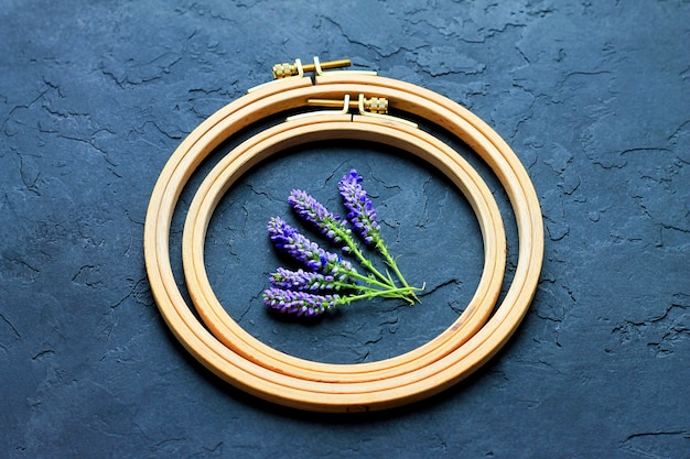 Wooden hoop on a dark background inside the hoop are blue flowers