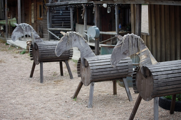 Wooden horses stand in the yard in the village. high quality photo