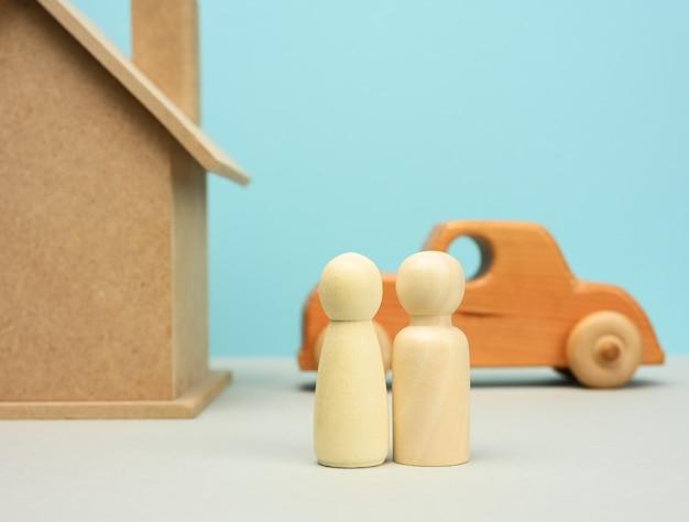 미니어처 가족 인물, 모기지 및 대출 개념을 가진 목조 주택과 자동차를 닫습니다.