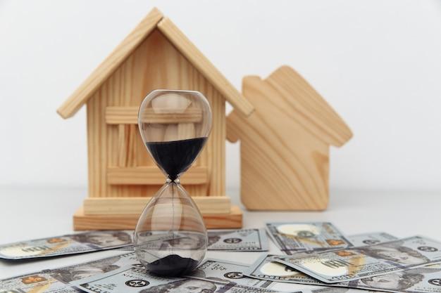 Деревянный дом и часы на долларовых банкнотах. покупка или продажа недвижимости.