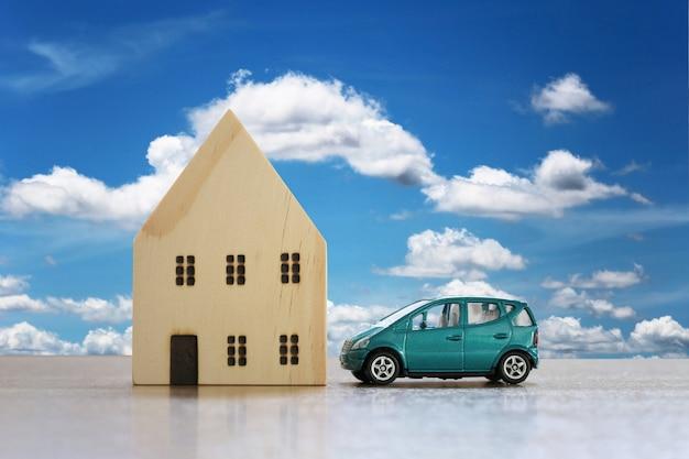 家と車としての財産を持つ床の概念上の木造住宅とおもちゃの車。