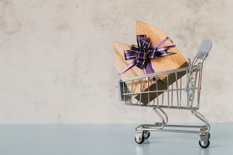 Wooden house blocks tied with purple ribbon bow inside the shopping cart against concrete wall