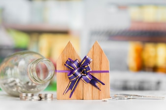 Wooden house blocks tied with ribbon bow with coins and keys on white table