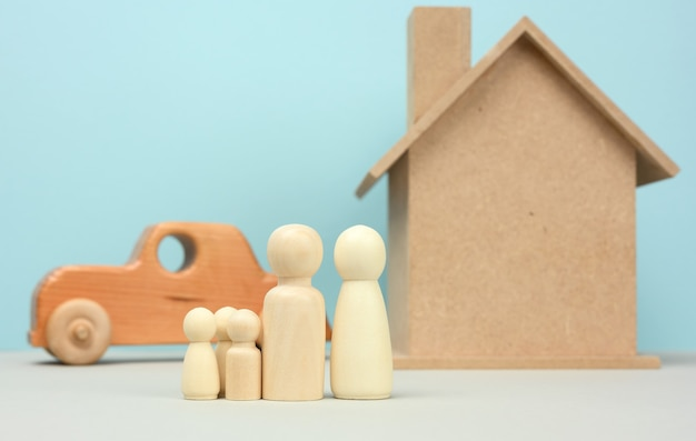 Wooden house and car with miniature family figures, mortgage and loan concept, close up