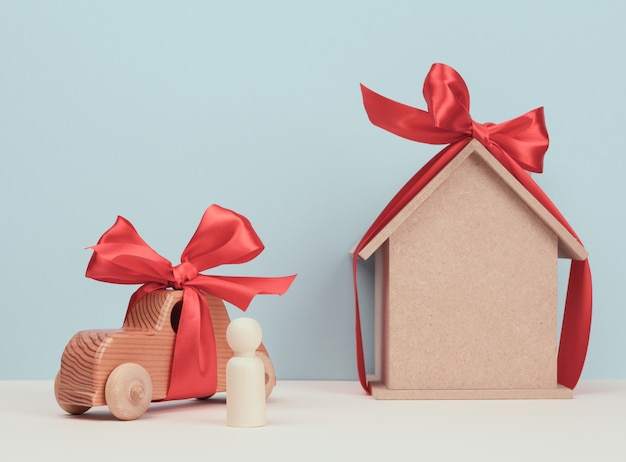 Wooden house and car with miniature wooden figurine of a man, mortgage and loan concept, close up