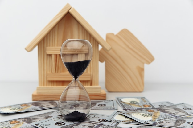 Wooden house and clock on dollar banknotes buying or selling real estate concept