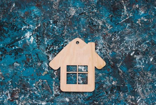 青いコンクリートの背景に木造住宅の置物またはキーホルダー。上面図