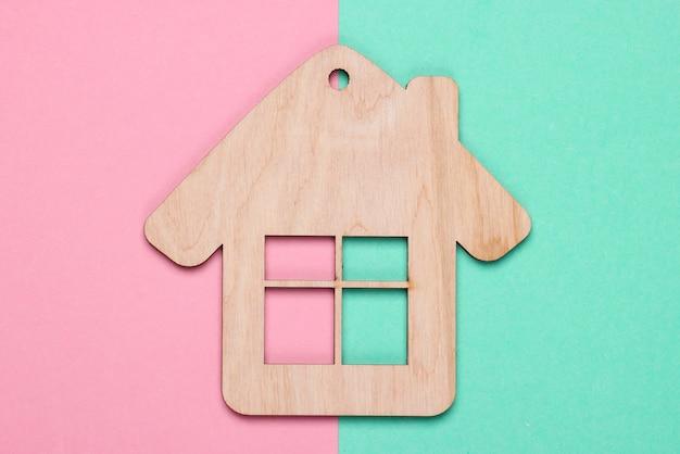 青ピンクの背景に木造住宅の置物またはキーホルダー。上面図