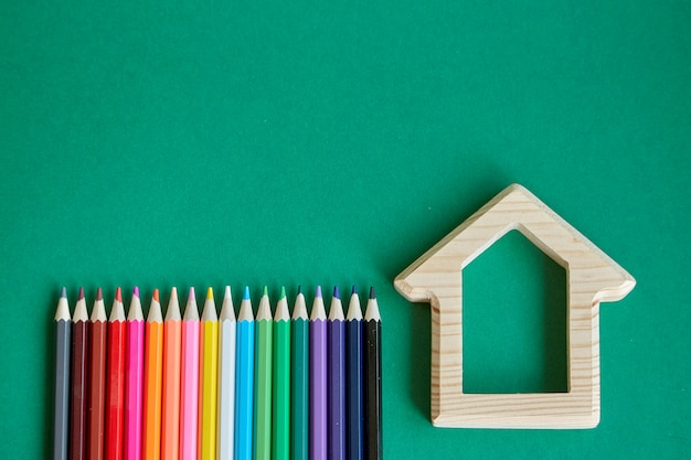 Wooden house figurine and several colored pencils isolate on green background