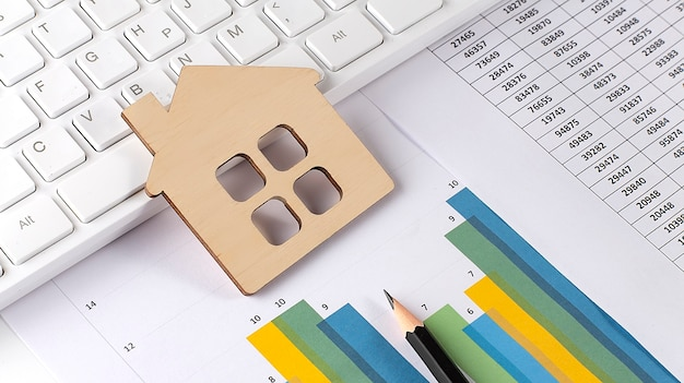 Wooden house on the graph with keyboard. economic chart. real estate market. mortgages.