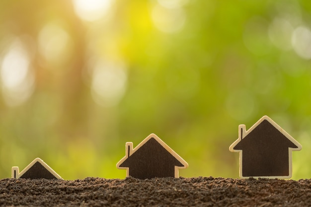 Wooden house growing in soil on green nature blur background. home business grow up concept