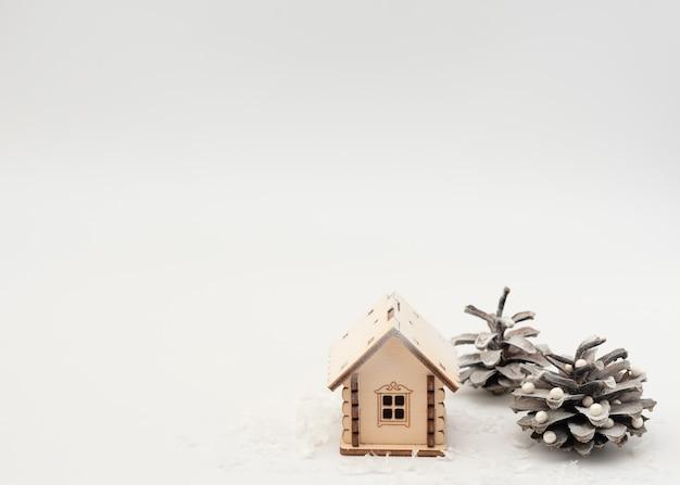 白地に飾られたクリスマスツリーのような松ぼっくりと雪の中の木造住宅