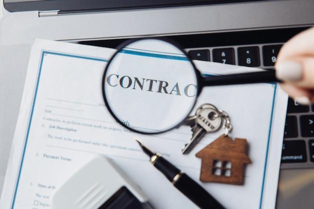 Деревянный дом, увеличительное стекло и контракт на ноутбуке. понятие аренды, поиска или ипотеки.