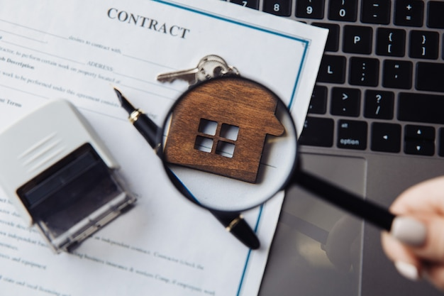 Wooden house, magnifying glass and contract on a laptop. concept of rent, search or mortgage. close-up.