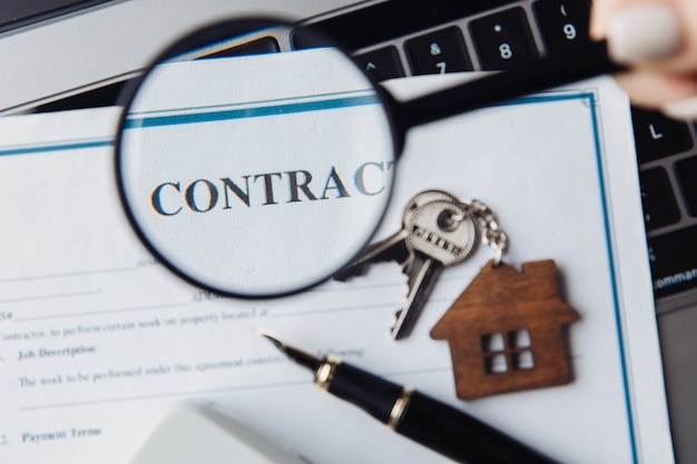 Wooden house, magnifying glass and contract