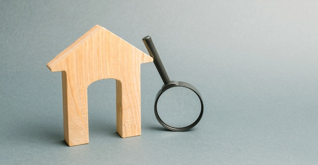 Wooden house and magnifying glass.