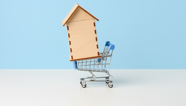 Wooden house in a metal miniature cart on a blue background. real estate purchase concept, mortgage