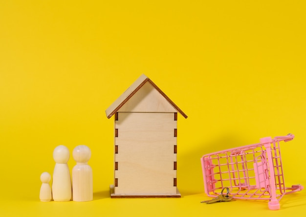 Wooden house and metal miniature cart on a yellow background. real estate purchase concept, mortgage