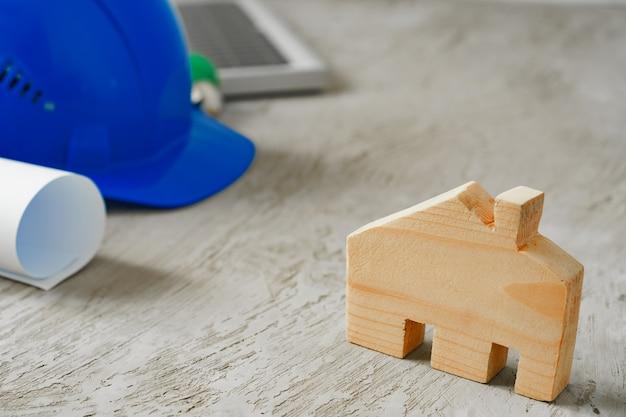 木製の家のミニチュアと木製のテーブルの青写真