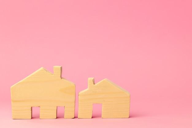 Деревянный домик в миниатюре на розовом фоне крупным планом фото