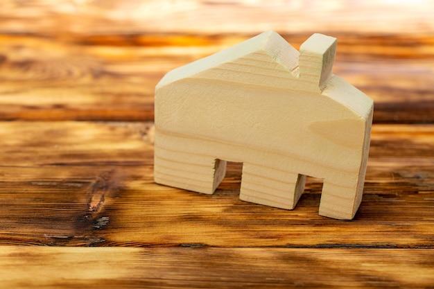 Миниатюрный деревянный дом на деревянной поверхности
