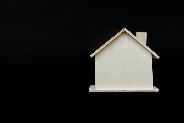 Wooden house model against black background