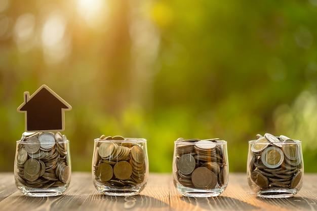 Модель и монета деревянного дома в ясном опарнике на деревянном столе. экономия денег для концепции дома
