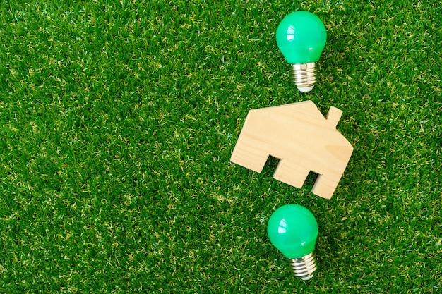 목조 주택 모델 및 녹색 배경에 전구