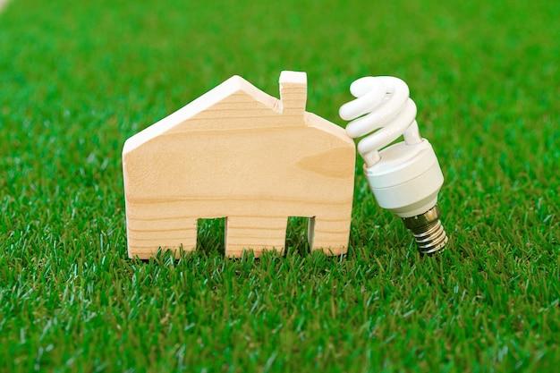 緑の背景に木造住宅モデルと電球