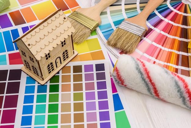 Модель деревянного дома и ролик на цветовой палитре