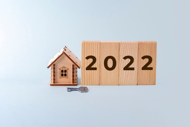 木造住宅モデル、碑文番号2022とキーのブロック。新年の家や不動産の売買の概念。住宅保険、不動産、住宅ローン。