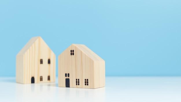 木造住宅モデルの青い背景、不動産事業の経済的成功。不動産投資のコンセプト。