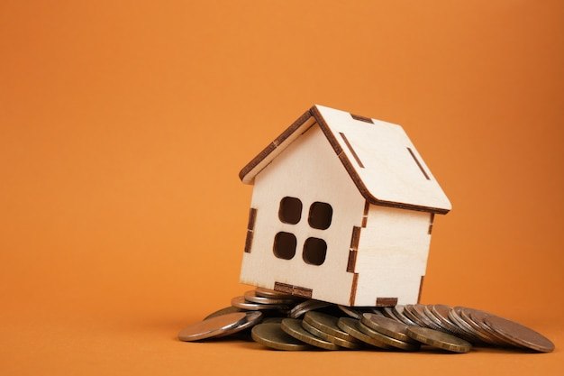 Wooden house model on coins on brown background
