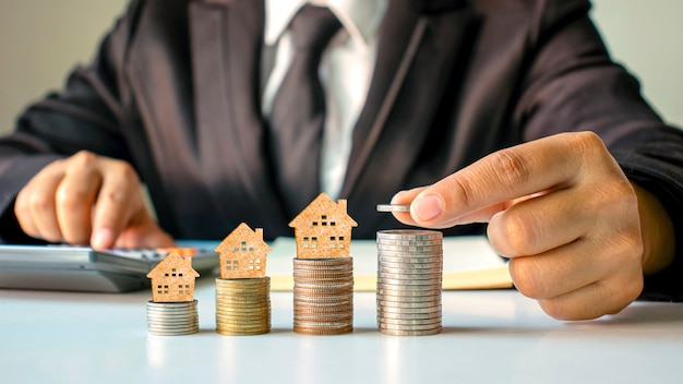 Wooden house model on coins and people's hands, real estate investment ideas and financial transactions.