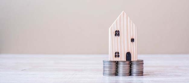 Wooden house model over coins stack on table background.