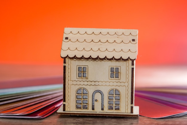 Wooden house model on colour background close