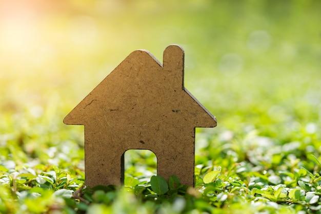 Wooden house model on fresh green grass background