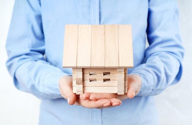 女性の手で木造住宅モデル。家のコンセプトを購入、賃貸、または抵当に入れる。