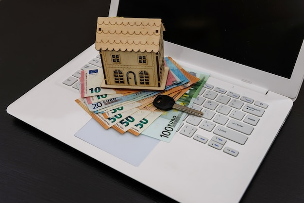 Wooden house model on laptop keyboard with euro