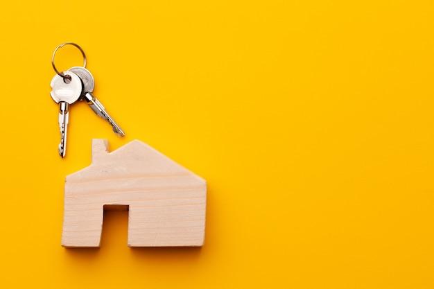 Миниатюрная модель деревянного дома и ключи от дома крупным планом