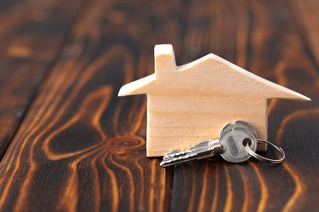 Миниатюрная модель деревянного дома и ключи от дома